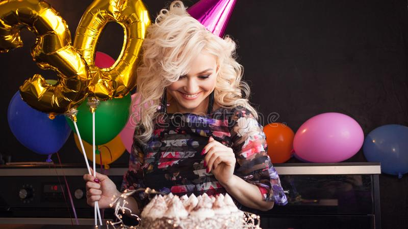 Happy young woman having fun at birthday party. Charming and attractive and festive cake. royalty free stock photography
