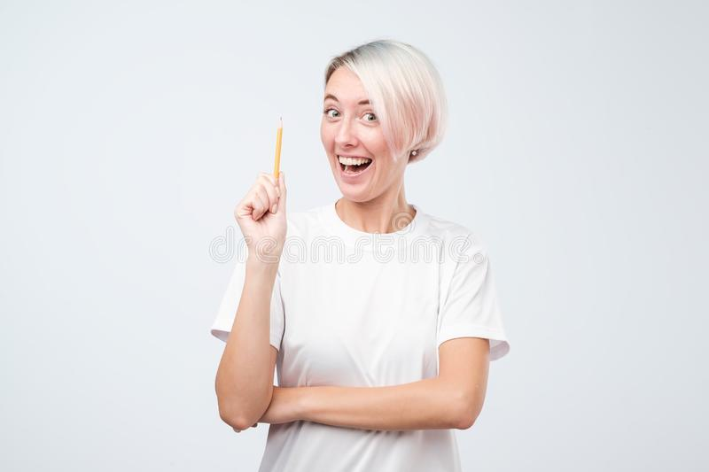 Happy young woman having idea and looking at the camera holding pencil. stock images