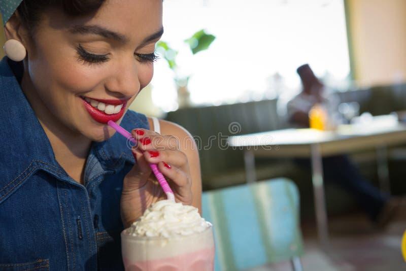 Happy young woman having milkshake in the restaurant royalty free stock image