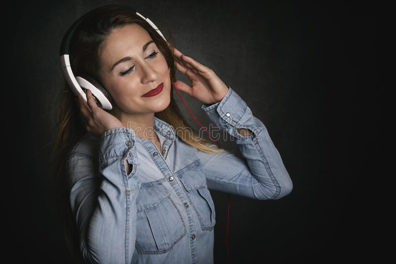 Happy young woman with headphones. On black background royalty free stock image