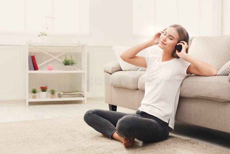 Happy young woman in headphones on floor stock image