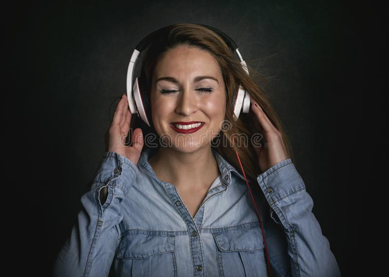 Happy young woman with headphones. On black background royalty free stock images