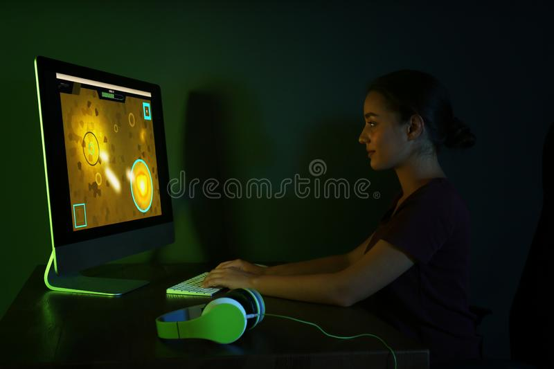 Happy young woman with headphones playing video game in room stock photo