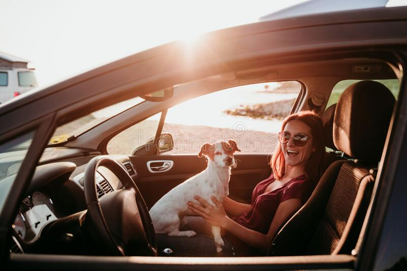 happy young woman and her cute jack russell dog in a car at sunset. travel concept stock image