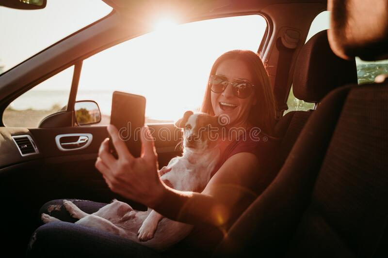 happy young woman and her cute jack russell dog in a car at sunset. travel concept stock photo