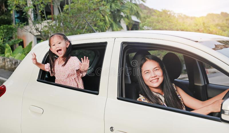 Happy young woman and her little child girl sitting in a car and looking camera from windows. Family travel concept stock images
