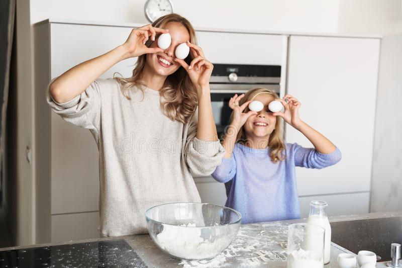 Happy young woman with her little sister indoors at home kitchen cooking with flour and eggs royalty free stock image