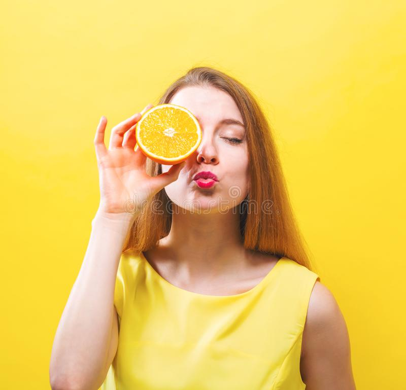 Free Happy Young Woman Holding A Half Orange Stock Photo - 109636630