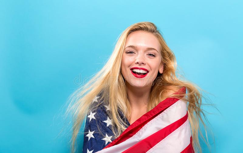 Happy young woman holding an American flag royalty free stock photo