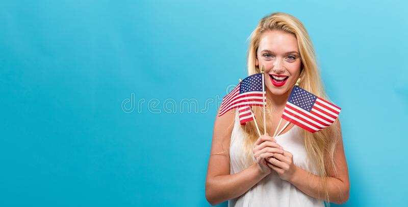 Happy young woman holding an American flag. On a blue background stock image