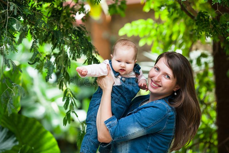 Happy young woman holding a baby out on a walk in the Park stock images