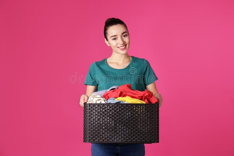 Happy young woman holding basket with clothes stock images