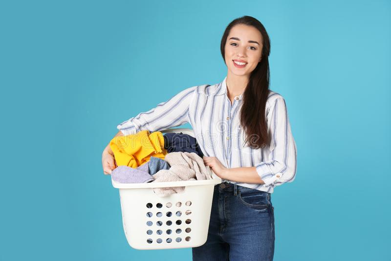 Happy young woman holding basket with laundry royalty free stock photos