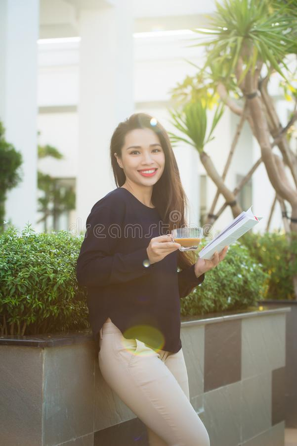 Happy young woman holding book fond of literature analyzing novel during leisure time on terrace of campus cafe in sunny day.  stock image