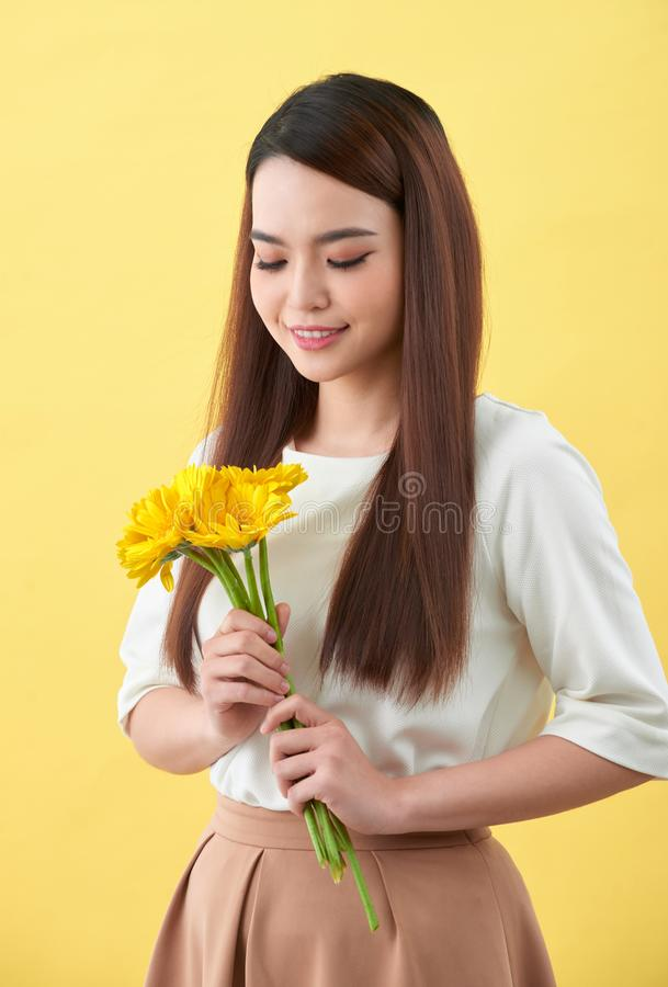 Happy young woman holding bouquet of flowers in her hand on yellow background.  stock photography