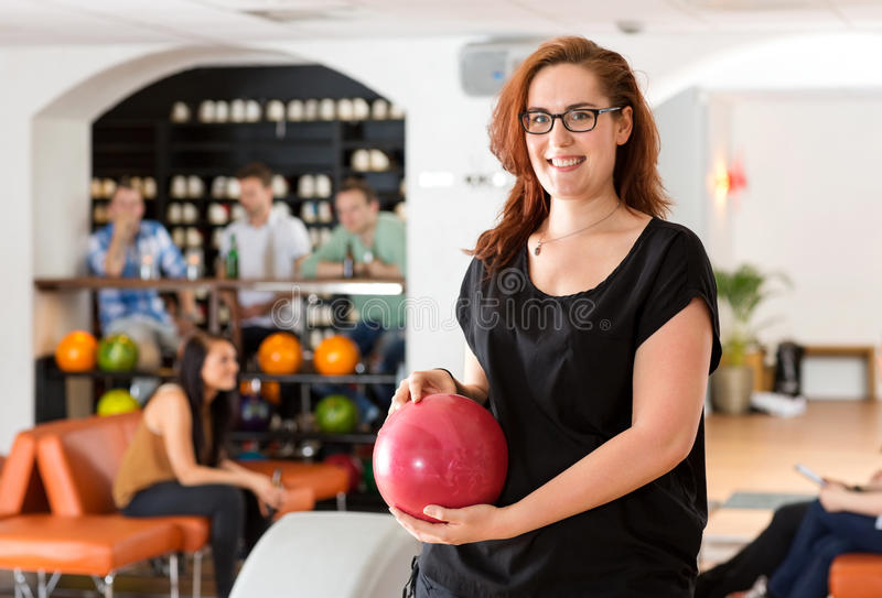 Happy Young Woman Holding Bowling Ball In Club Royalty Free Stock Images