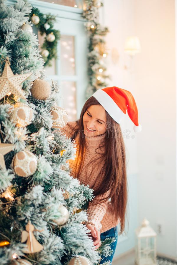 Happy young woman holding Christmas ball in front of Christmas tree.  royalty free stock images