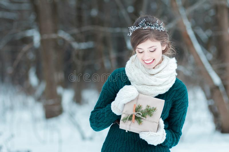 Happy young woman holding Christmas gift. In hands royalty free stock images