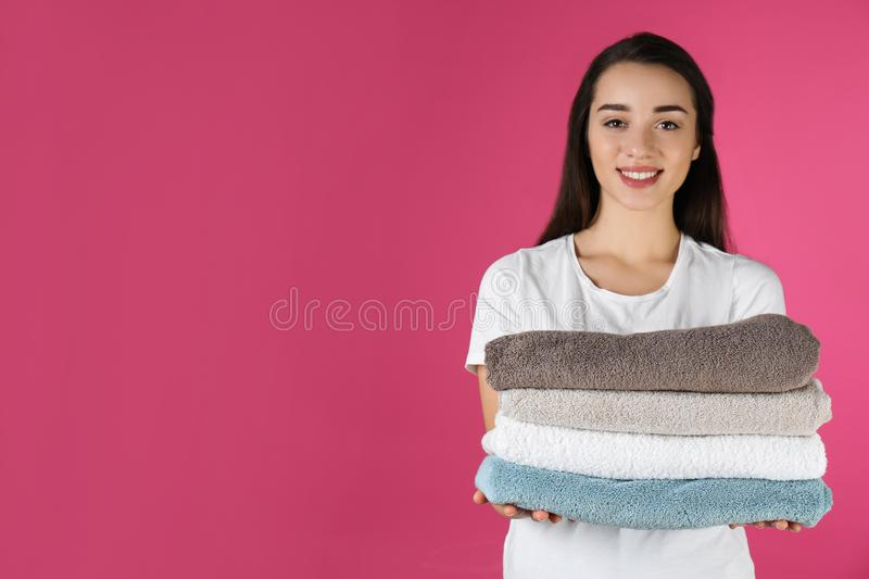 Happy young woman holding clean towels on color background. Laundry day. Happy young woman holding clean towels on color background, space for text. Laundry day royalty free stock photo