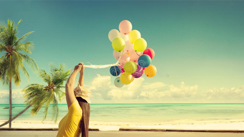 Happy young woman holding colorful balloons with floating, stock photography