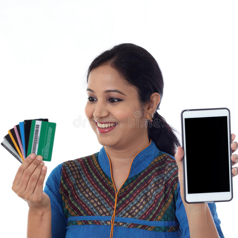 Happy young woman holding debit cards and cellphone stock image