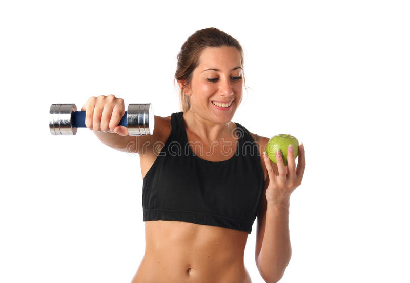 Happy young woman holding a dumbbell and a green apple stock photos