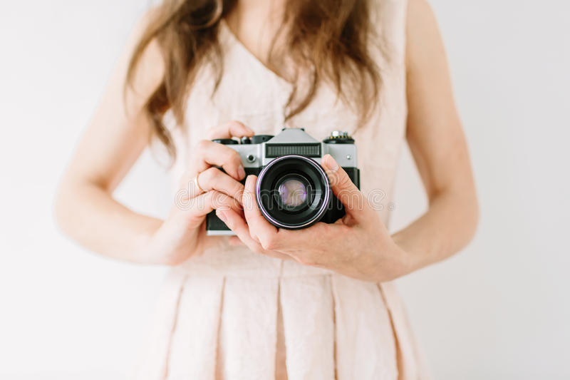 Happy young woman holding in hands old vintage camera. Girl photographer stock photos