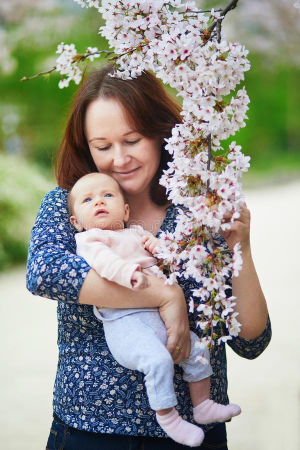 Happy young woman holding her little baby girl stock image