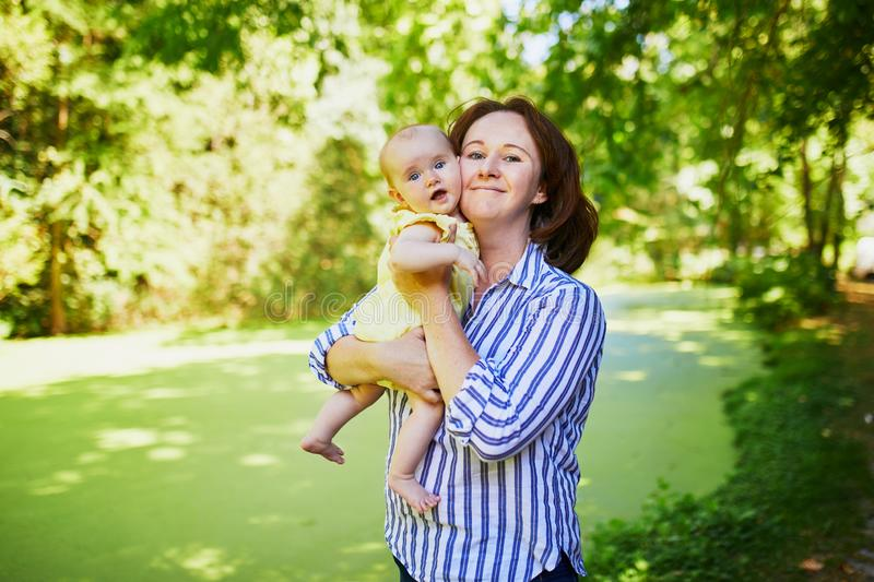 Happy young woman holding her little baby girl outdoors royalty free stock image