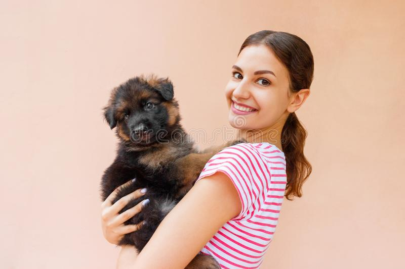 Happy young woman holding her pet puppy on orange background stock photos