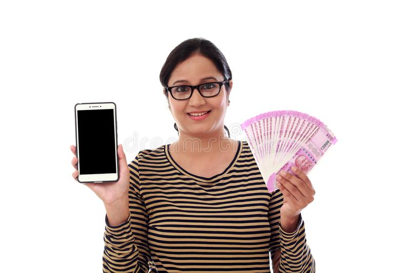 Happy young woman holding Indian currency and mobile phone royalty free stock images
