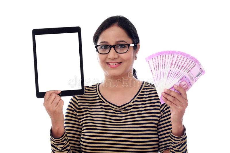 Happy young woman holding Indian currency and tablet computer royalty free stock images