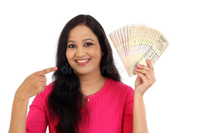 Happy young woman holding Indian rupee bank notes. Against white background royalty free stock photo
