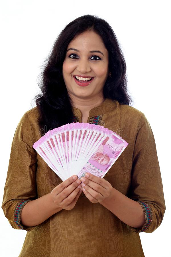 Happy young woman holding Indian 2000 rupee notes royalty free stock photos
