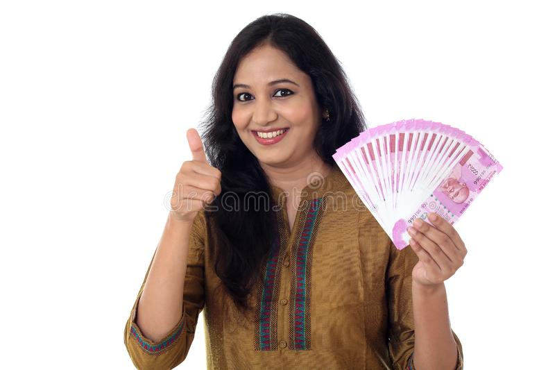 Happy young woman holding Indian 2000 rupee notes royalty free stock images