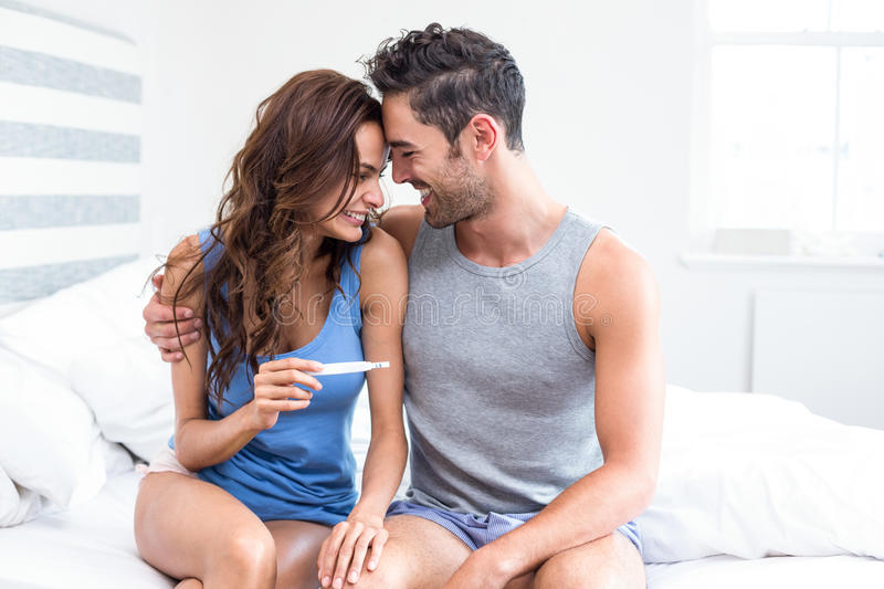Happy young woman holding pregnancy test sitting besides husband royalty free stock images