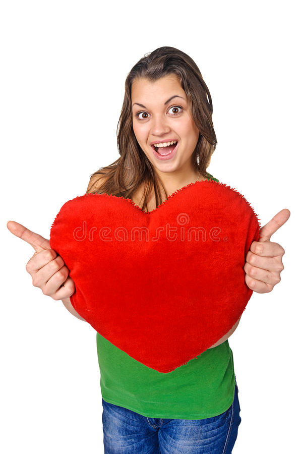 Happy young woman holding red heart shaped pillow stock image