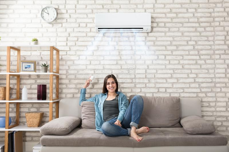 Woman Relaxing Under The Air Conditioner. Happy Young Woman Holding Remote Control Relaxing Under The Air Conditioner royalty free stock image