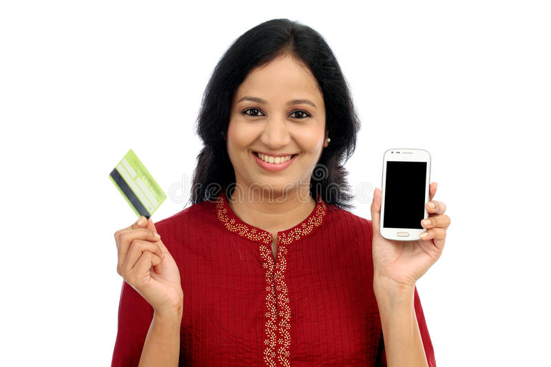 Happy young woman holding smart phone and credit card royalty free stock photo