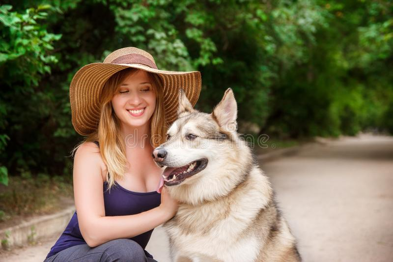 Happy young woman hugs siberian husky in the park. The concept of care and walking with a dog royalty free stock image