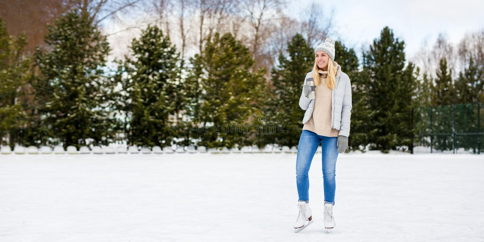 Happy young woman in ice skates posing with coffee cup at rink in winter park - copy space over ice. Portrait of happy young woman in ice skates posing with royalty free stock photos