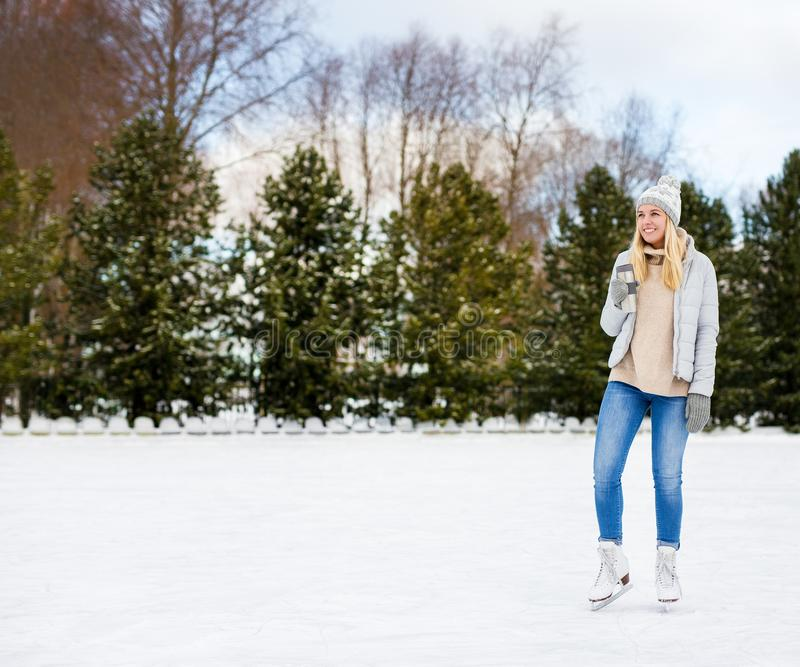 Happy young woman ice skating and drinking coffee at rink in winter park - copy space over ice. Portrait of happy young woman ice skating and drinking coffee at stock photography