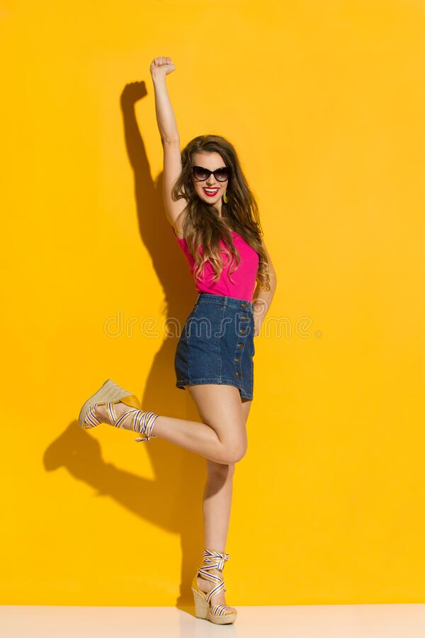 Free Happy Young Woman In Mini Skirt Is Standing On One Leg With Arm Raised Stock Image - 179977091