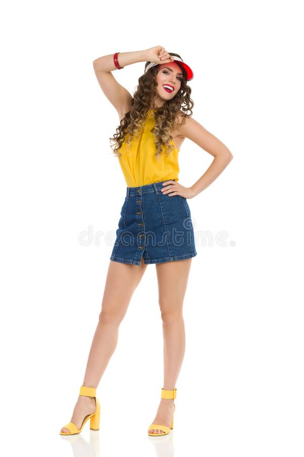 Happy Young Woman In Jeans Mini Skirt And High Heels Is Posing In Red Sun Visor Cap. Confident young woman in jeans mini skirt, yellow top and high heels is royalty free stock photos