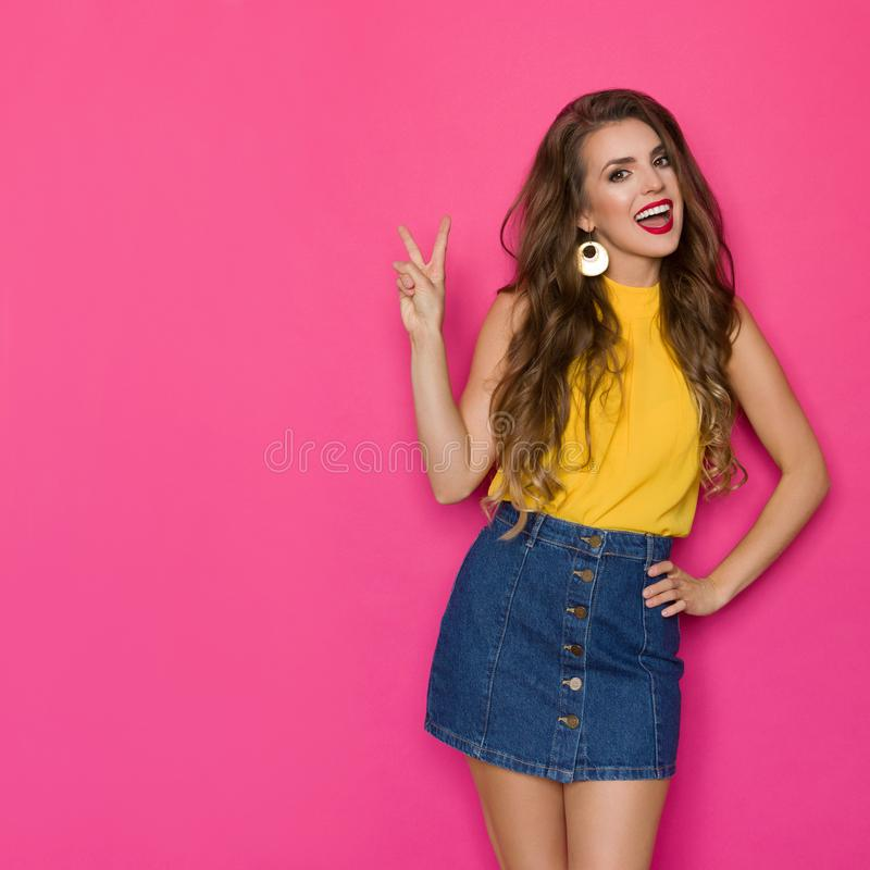 Happy Young Woman In Jeans Mini Skirt And Yellow Top Is Talking And Showing Peace Hand Sign. Happy young woman in jeans mini skirt and yellow top is showing royalty free stock photography