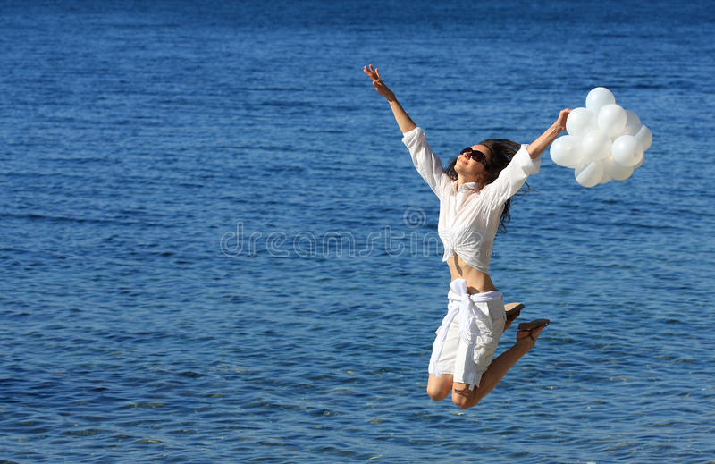 Happy young woman jumping above the sea stock photos