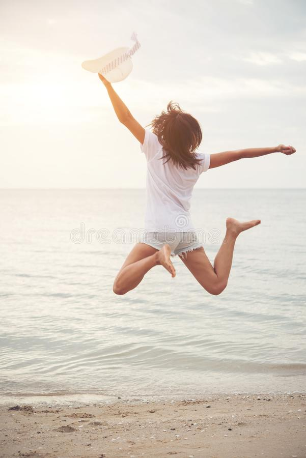 Happy young woman jumping on the beach. Freedom enjoy with vacation, Women lifestyle concept. royalty free stock photo