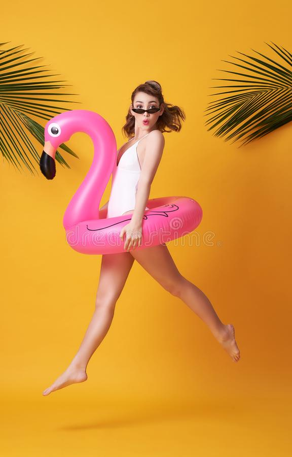 Happy young woman jumping on yellow background dressed in swimwear holding flamingo rubber ring beach stock images