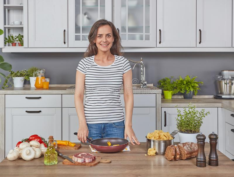 Happy young woman in the kitchen stock image
