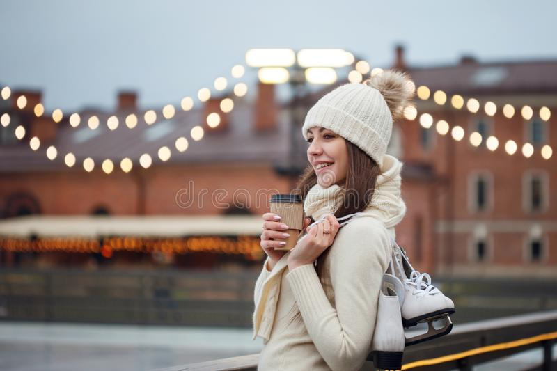Happy young woman in knitted sweater and hat is going skating stock image